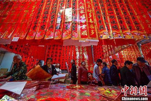 """资料图:海南海口""""小年""""购年货,红火迎春节。中新社记者 骆云飞 摄"""